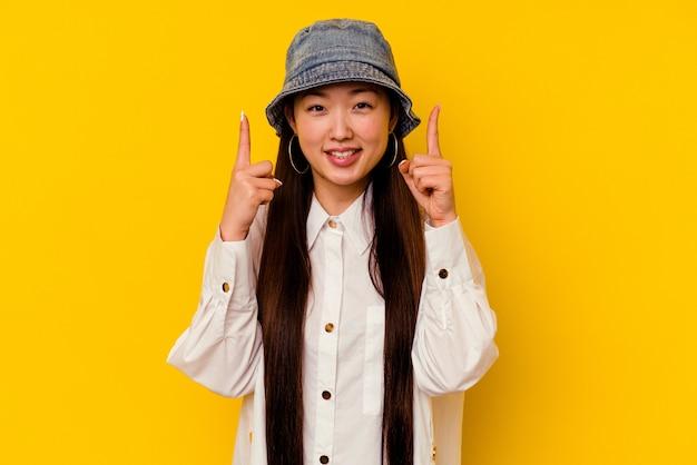 Młoda chinka na białym tle na żółtym tle wskazuje obiema palcami przednimi do góry, pokazując puste miejsce.