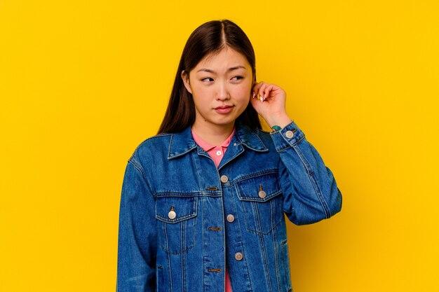 Młoda chinka na białym tle na żółtym tle zakrywających uszy palcami, zestresowana i zdesperowana głośnym otoczeniem.