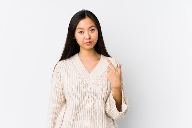Młoda chinka na białym tle wskazując palcem na ciebie, jakby zapraszając podejść bliżej.