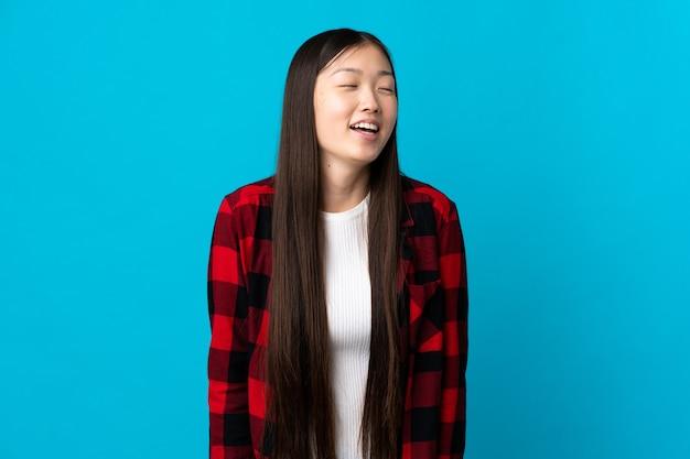 Młoda chinka na odosobnionym niebieskim śmiechu