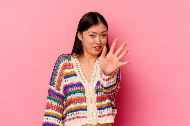 Młoda chinka na różowej ścianie odrzuca kogoś, kto pokazuje gest obrzydzenia.