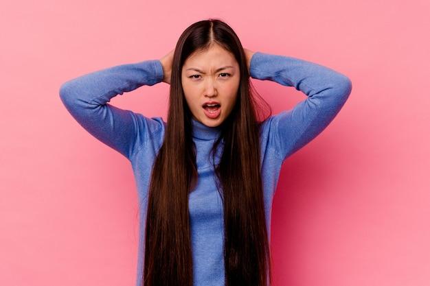 Młoda chinka na różowym tle krzyczy z wściekłości.