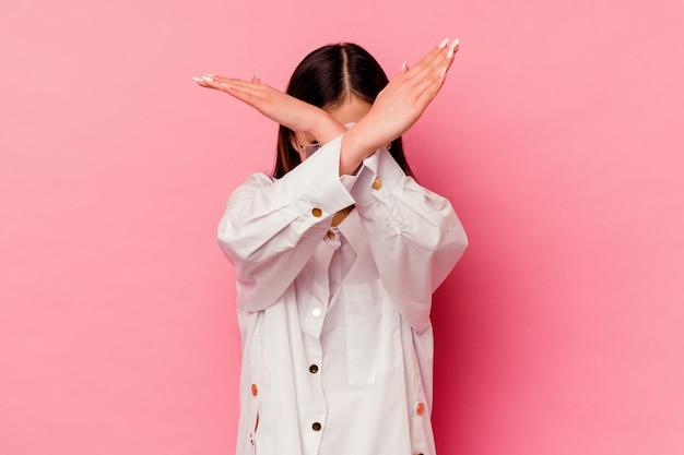 Młoda chinka na różowym tle, trzymając skrzyżowane ręce, koncepcja odmowy.