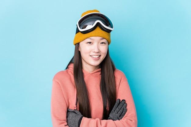 Młoda chinka na sobie ubrania narciarskie na białym tle śmiechu i zabawy.