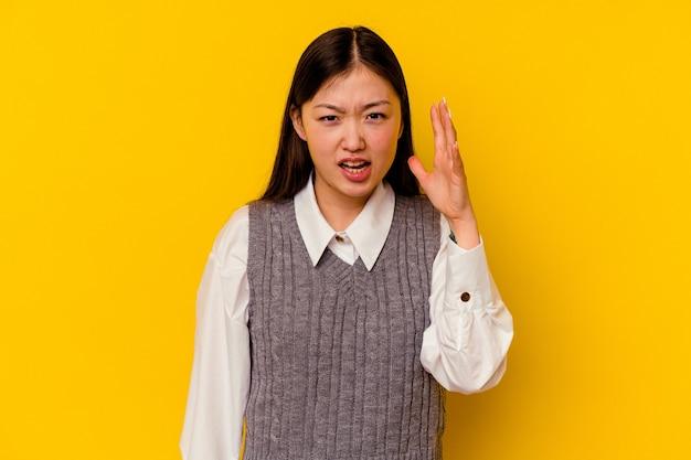 Młoda chinka na żółtym tle krzyczy z wściekłości.