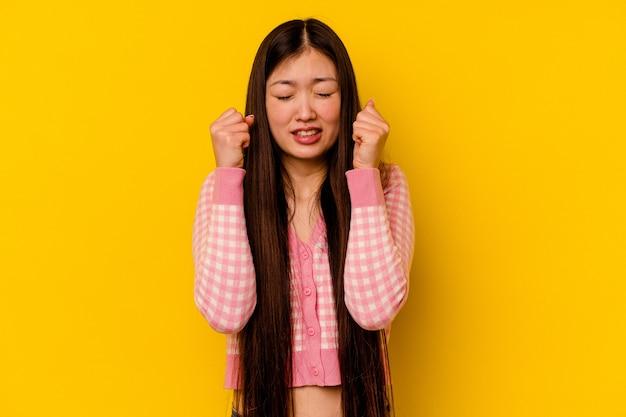 Młoda chinka na żółtym tle świętuje zwycięstwo, pasję i entuzjazm, szczęśliwy wyraz.