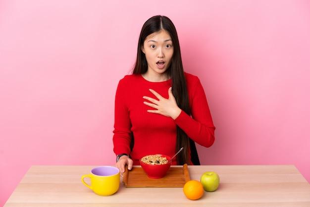 Młoda chinka o śniadanie w tabeli zaskoczona i zszokowana, patrząc w prawo