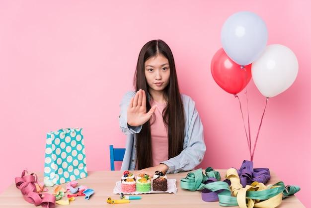 Młoda chinka organizowanie urodziny na białym tle stojący z wyciągniętą ręką pokazując znak stop, zapobiegając ci.