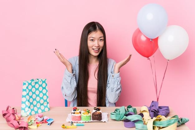 Młoda chinka organizująca urodziny otrzymała miłą niespodziankę, podekscytowana i podnosząca ręce.