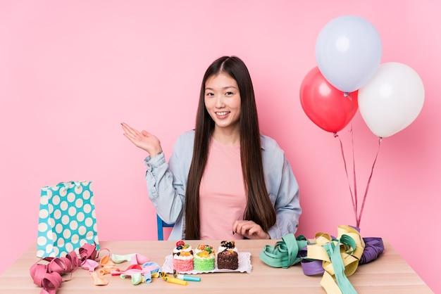 Młoda chinka organizuje urodziny na białym tle pokazując miejsce na kopię na dłoni i trzymając drugą rękę na talii.