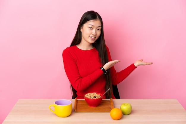 Młoda chinka po śniadaniu w stole rozkładającym ręce na bok, zapraszając do siebie