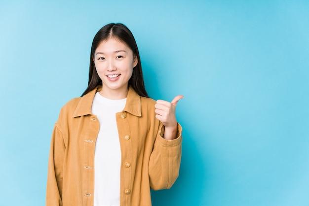 Młoda chinka pozowanie na niebieskim tle na białym tle uśmiechnięty i podnoszący kciuk do góry