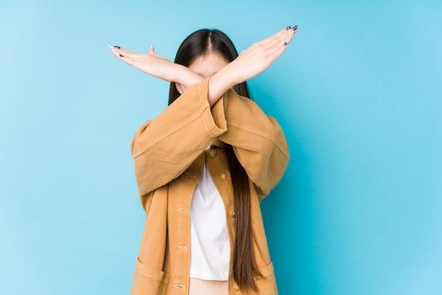 Młoda chinka pozowanie na niebiesko na białym tle, trzymając dwa skrzyżowane ręce