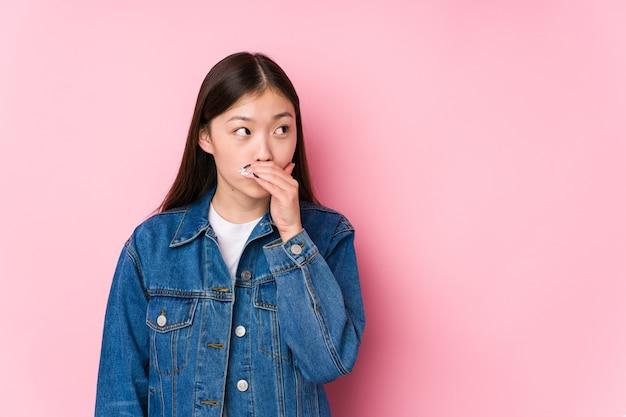 Młoda chinka pozowanie na różowym tle na białym tle zamyślony patrząc na przestrzeń kopię obejmującą usta ręką.