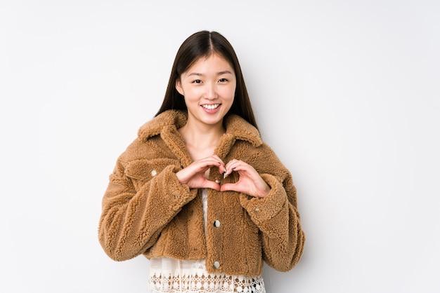 Młoda chinka pozowanie w białej przestrzeni na białym tle uśmiechając się i pokazując kształt serca rękami.