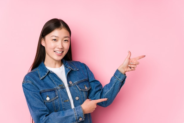 Młoda chinka pozowanie w różowej ścianie na białym tle podekscytowany, wskazując palcami wskazującymi z dala.