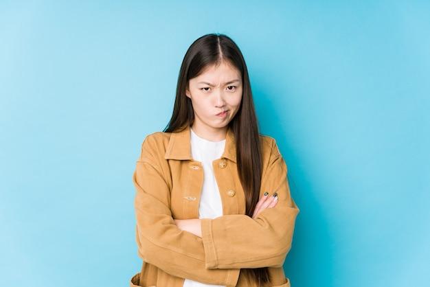 Młoda chinka pozuje na niebiesko odizolowanej twarzy marszczącej brwi z niezadowoleniem, trzyma założone ręce.