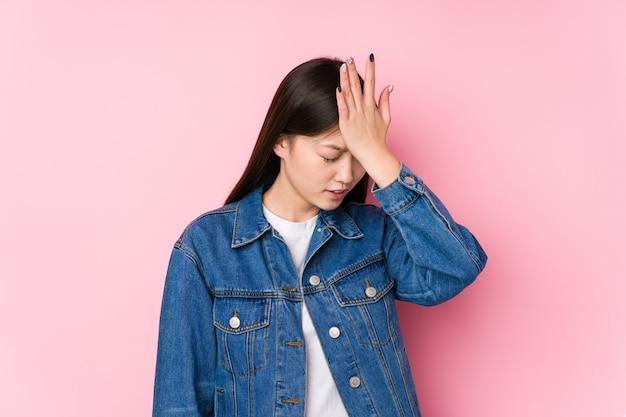 Młoda chinka pozuje na różowo na białym tle zapominając o czymś, uderzając dłonią w czoło i zamykając oczy.