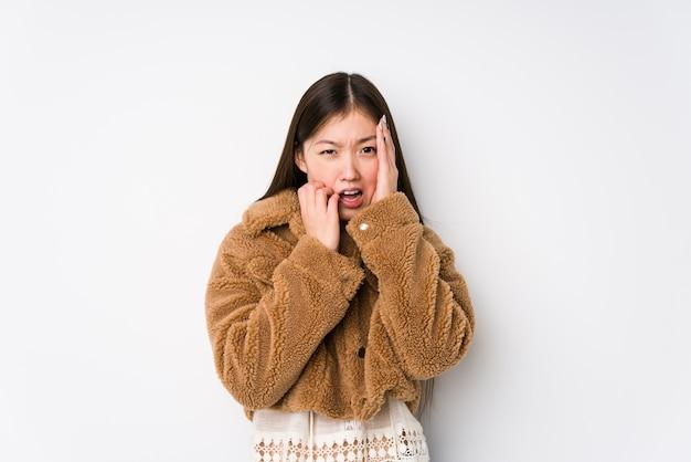 Młoda chinka pozuje w białej ścianie na białym tle skomlenie i płacz niepocieszony.