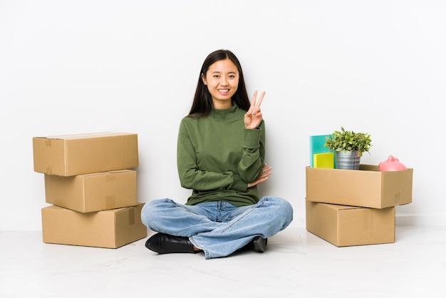 Młoda chinka przenosi się do nowego domu pokazuje numer dwa palcami.