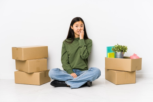Młoda chinka przeprowadzająca się do nowego domu obgryzająca paznokcie, nerwowa i bardzo niespokojna.