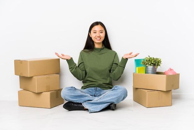 Młoda chinka przeprowadzająca się do nowego domu robi wagę z rękami, czuje się szczęśliwa i pewna siebie.