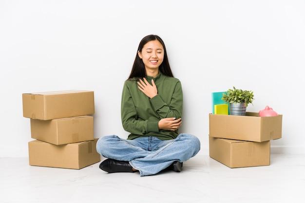 Młoda chinka przeprowadzająca się do nowego domu śmieje się radośnie i bawi się, trzymając ręce na brzuchu.