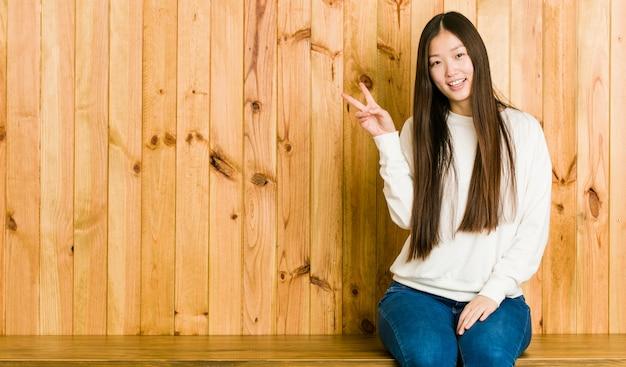Młoda chinka siedzi na drewniane miejsce radosny i beztroski, pokazując symbol pokoju palcami.