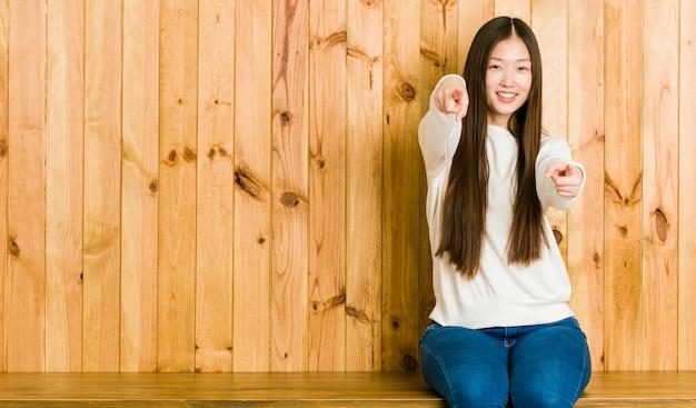 Młoda chinka siedzi na drewniane miejsce wesoły uśmiechy, wskazując na przód.