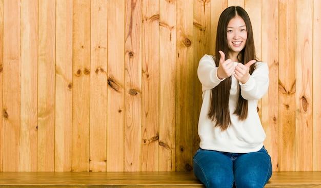 Młoda chinka siedzi na drewniane miejsce z kciuki do góry, na zdrowie o coś