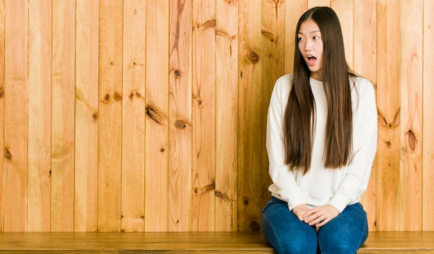 Młoda chinka siedzi na drewnianym miejscu jest zszokowany przez coś, co widziała.
