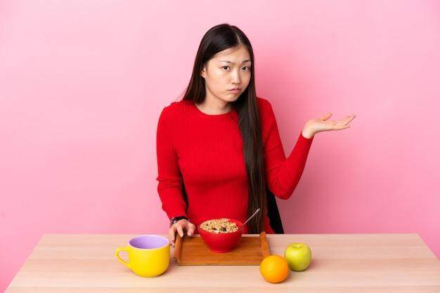 Młoda chinka śniadanie w stole ma wątpliwości