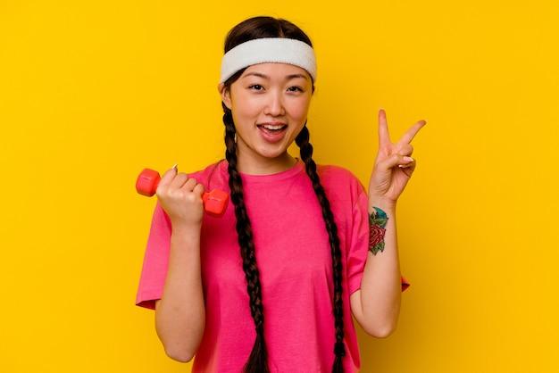 Młoda chinka sport odizolowana na żółtym tle radosna i beztroska pokazująca palcami symbol pokoju.