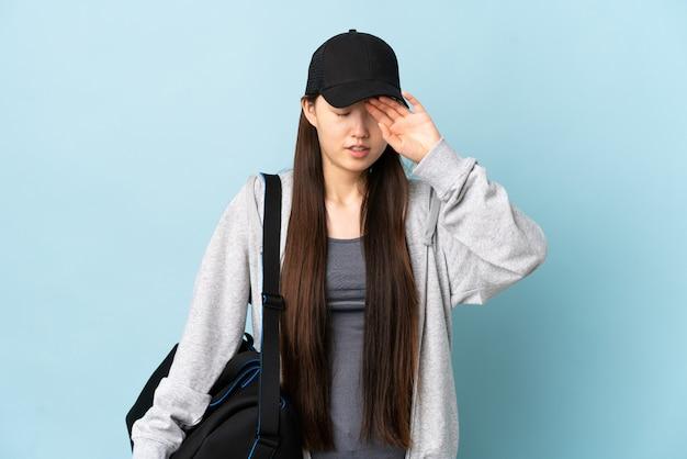 Młoda chinka sportowa z torbą sportową na białym tle niebieski z wyrazem zmęczenia i choroby