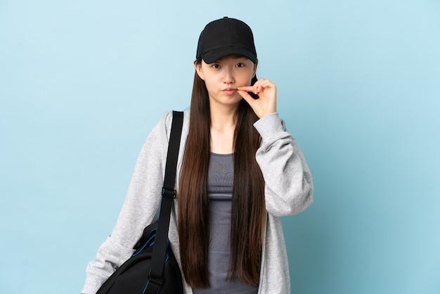 Młoda chinka sportowa z torbą sportową na niebiesko wykazujące znak gestu ciszy