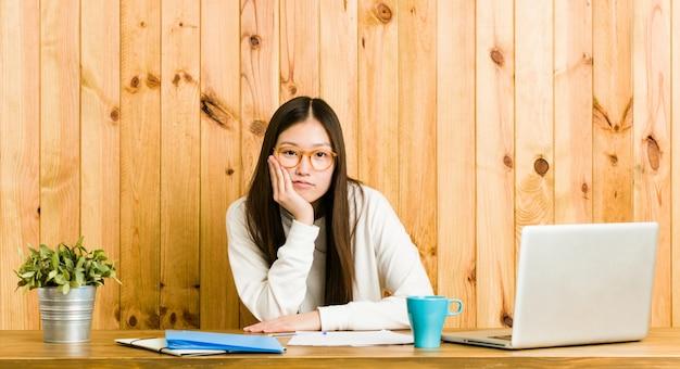 Młoda chinka studiuje na biurku, który jest znudzony, zmęczony i potrzebuje dnia relaksu.