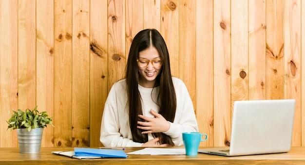 Młoda chinka studiuje na biurku, śmieje się radośnie i dobrze się trzyma, trzymając ręce na brzuchu.