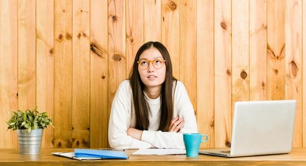 Młoda chinka studiuje na biurku zmęczonym powtarzającym się zadaniem.