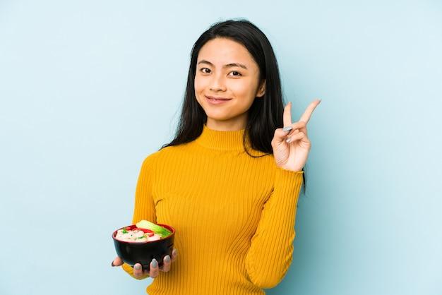 Młoda chinka trzyma miskę makaronu