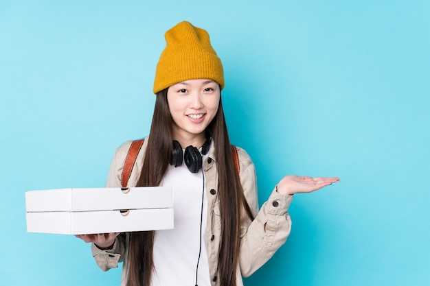 Młoda chinka trzyma pizze na białym tle, pokazując miejsce na kopię na dłoni i trzymając drugą rękę na talii.