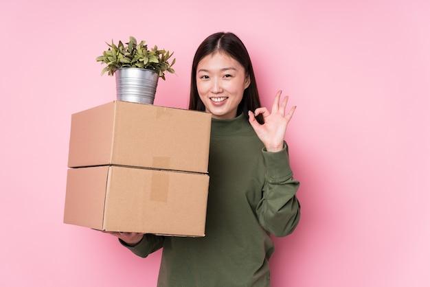 Młoda chinka trzyma pudełka na białym tle wesoły i pewny siebie, pokazując ok gest.