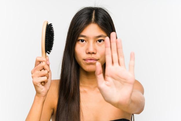 Młoda chinka trzyma szczotkę do włosów na białym tle stojąc z wyciągniętą ręką pokazując znak stopu, uniemożliwiając ci.