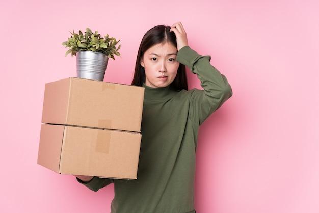 Młoda chinka trzymająca pudełka na białym tle będąc w szoku, przypomniała sobie ważne spotkanie.