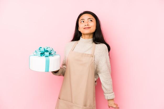 Młoda chinka trzymająca tort na białym tle zaskoczona i zszokowana.