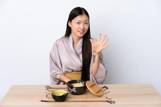 Młoda chinka ubrana w kimono i je makaron, licząc pięć palcami