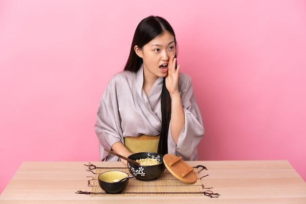 Młoda chinka ubrana w kimono i jedząca makaron, krzycząca z szeroko otwartymi ustami