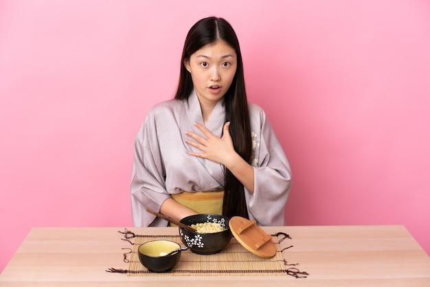 Młoda chinka ubrana w kimono i jedząca makaron zaskoczona i zszokowana, patrząc w prawo