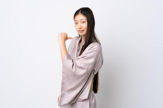 Młoda chinka ubrana w kimono jest dumna i zadowolona z siebie