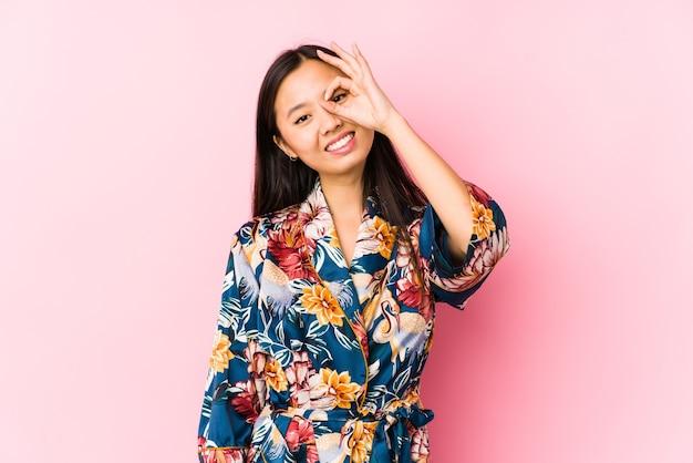Młoda chinka ubrana w kimono piżamę na białym tle podekscytowany utrzymując ok gest na oko.