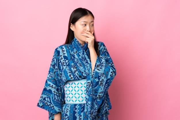 Młoda chinka ubrana w kimono robi gest niespodzianki, patrząc w bok